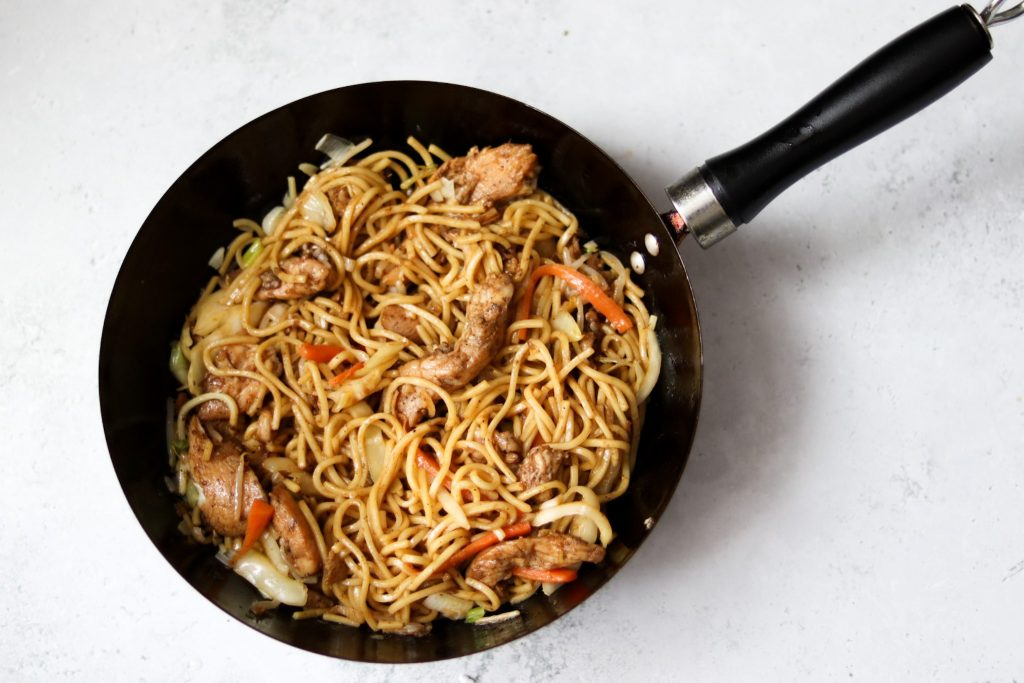 Homemade chicken chow mein in a pan with the chow mein sauce on top.